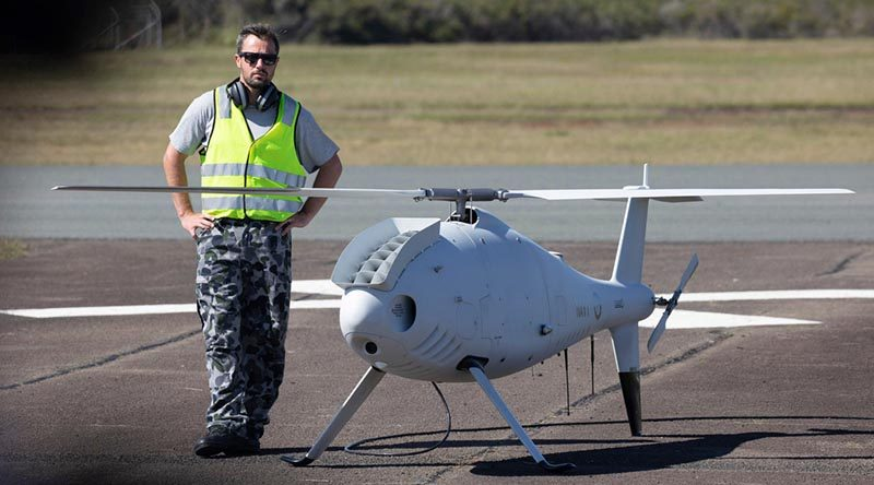 Petty Officer Aviation Technician Avionics Rodney Ferreira, stands by the Schiebel S-100 Camcopter prior to its flight at Jervis Bay airfield. Photo by Chief Petty Officer Cameron Martin.