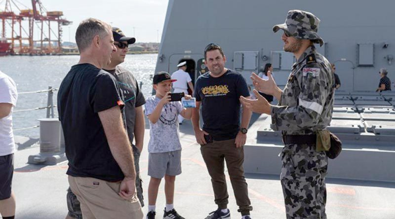 Able Seaman Electronics Technician Liam Walker talks about HMAS Hobart's 5-inch gun with attendees of the HMAS Hobart Open Day during a port visit in Melbourne, Victoria. Photo by Able Seaman Jarrod Mulvihill.