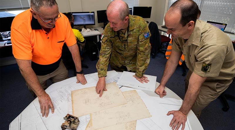 Colonel Bradley Robertson and Warrant Officer Class Two Steven Cosstick discuss options for making a replacement part for a surgical-mask manufacturing machine with David Mather at Med-Con Pty Ltd, a small manufacturer in Regional Victoria. Photo by Corporal Sagi Biderman.