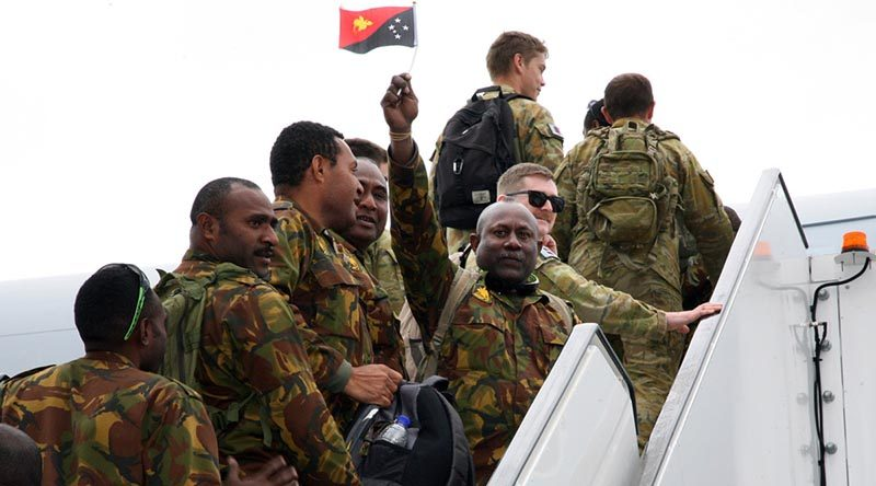 A Papua New Guinea Defence Force soldier proudly waves his nation's flag as he and fellow Task Group Dingo members board a Royal Australian Air Force KC-30 Multi-Role Tanker Transport aircraft at Tullamarine Airport on their way home. Photo by Major Cameron Jamieson.