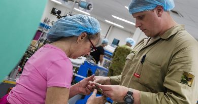 Australian Army soldier Corporal Sander Vloothuis and Med-Con employee Lynn Stockwell inspect a surgical face mask off the production line. Photo by Corporal Sagi Biderman.