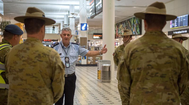 Inspector Peter Aitken from the Queensland Police Service briefs an Australian Army contingent from the 9th Battalion, Royal Queensland Regiment, supporting mandatory COVID-19 quarantine arrangements for international travellers at Brisbane Airport. Photo by Trooper Jonathan Goedhart.