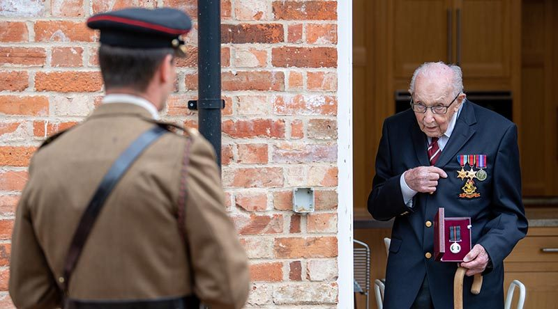 Colonel Tom Moore talks to Lieutenant Colonel Thomas Miller while holding The Yorkshire Regiment Medal, re-presented as a birthday gift from the British Army after he lost the original. Photo by Corporal Robert Weideman, UK Ministry of Defence.