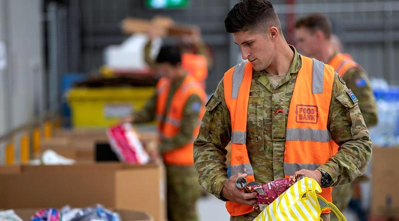 Australian Army soldier Private Jack Barrie sorts donations at the Foodbank warehouse in Glendenning, NSW, as part of Defence's Operation COVID-19 Assist. Photo by Corporal Chris Beerens.