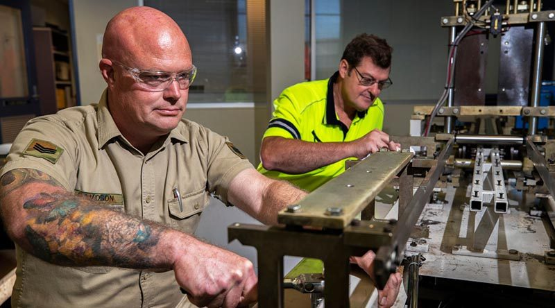 Australian Army soldier Sergeant Steven Davidson assists Bob Neighbour to repair a medical mask manufacturing machine at Med-Con Pty Ltd. Photo by Corporal Sagi Biderman.