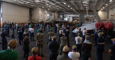 Crew of the USS Theodore Roosevelt listen to Vice Admiral William Merz, commander US 7th Fleet, answering questions during a visit to the ship on 7 April 2020. US Navy photo by Mass Communication Specialist Seaman Kaylianna Genier.
