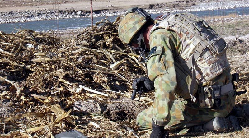 Flight Sergeant Damian Holding conducting a search for unexploded ordnance in Afghanistan.
