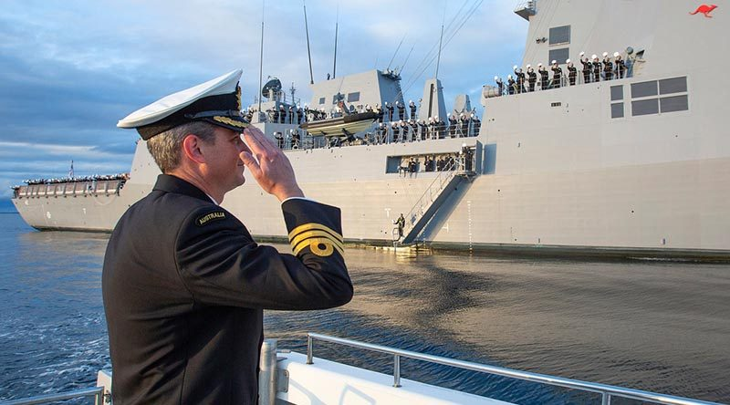 Commanding Officer HMAS Sydney (V) Commander Edward Seymour salutes his crew inside Jervis Bay, NSW, following the ship's commissioning ceremony at sea. Photo by Petty Officer Tom Gibson.