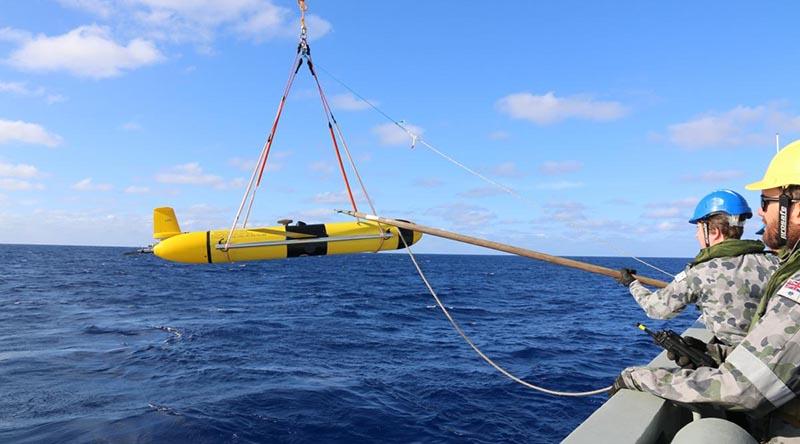 HMAS Melville crewmembers deploy a Slocum Glider.