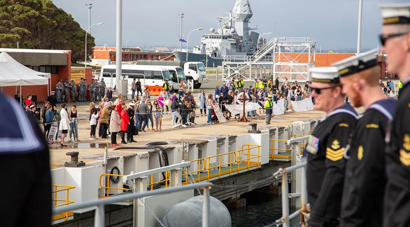 Friends and family of HMAS Toowoomba's ship's company line the wharf as the ship berth's alongside Parkes Wharf, HMAS Stirling, Western Australia. Photo by Able Seaman Lincoln Commane.