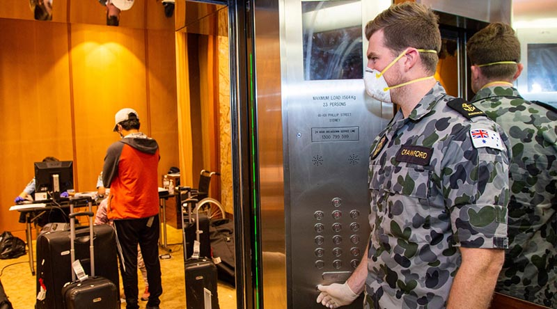 Leading Seaman Michael Crawford waits in a lift of a Sydney hotel to assist travellers going into mandatory 14-day quarantine. Around 850 of 1000 ADF member being deployed to Victoria will be assigned to similar duties in Melbourne. Photo by Petty Officer Justin Brown.