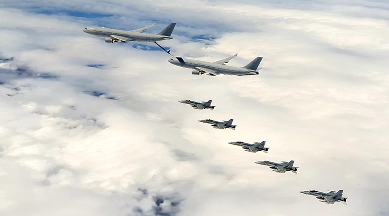 F/A-18A Hornets fly in formation with KC-30A multirole tanker transports enroute to Guam. RAAF photo.