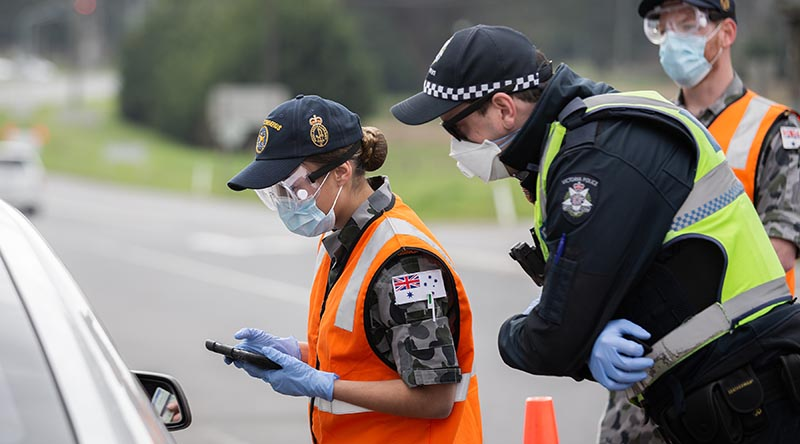 Royal Australian Navy Seaman Kirie South, from HMAS Cerberus, checks a driver's details at a vehicle control point in Victoria, assisting the Victoria Police Force during Op COVID-19 Assist. Photo by Leading Aircraftman John Solomon.