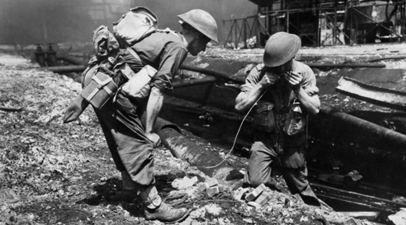 Sappers of the 2/4th Field Company prepare to blow up pipe lines obstructing the movement of tanks supporting the advance through the oil refinery area at Balikpapan. AWM 128776