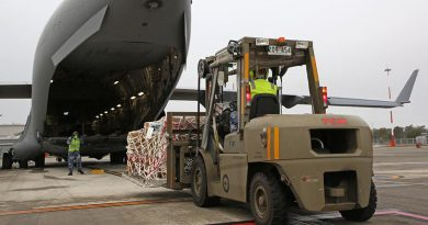 Aircraftman Joseph Freeman directs forklift driver Leading Aircraftman Christopher Wettenhall from No. 23 Squadron, during the physical loading of virtual conferencing systems onto a No. 36 Squadron C-17A Globemaster III bound for Fiji. Photo by Corporal Colin Dadd.