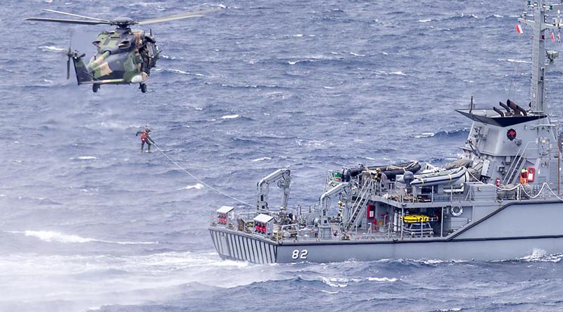 HMAS Choules' embarked MRH-90 Taipan helicopter conducts passenger transfer serials with HMAS Huon during the ships' transit to Vanuatu. Photo by Leading Seaman James McDougall.