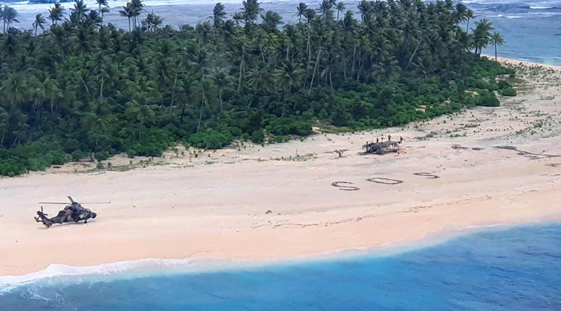 An Australian Army ARH Tiger helicopter lands on Pikelot Island in Micronesia. The SOS message of the stricken sailors can be seen on the beach. ADF photo.