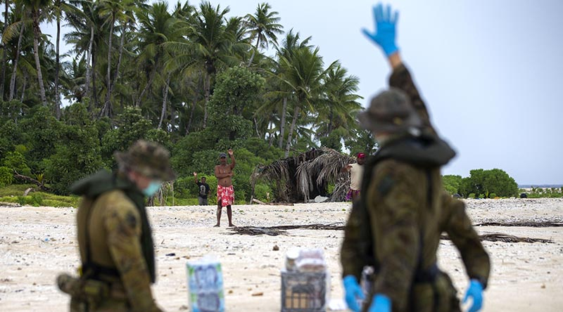 Australian soldiers from 2RAR, keeping their distance because of COVID-19, deliver supplies to three Micronesian mariners stranded on a small island awaiting rescue. Photo by Leading Seaman Kieren Whiteley.