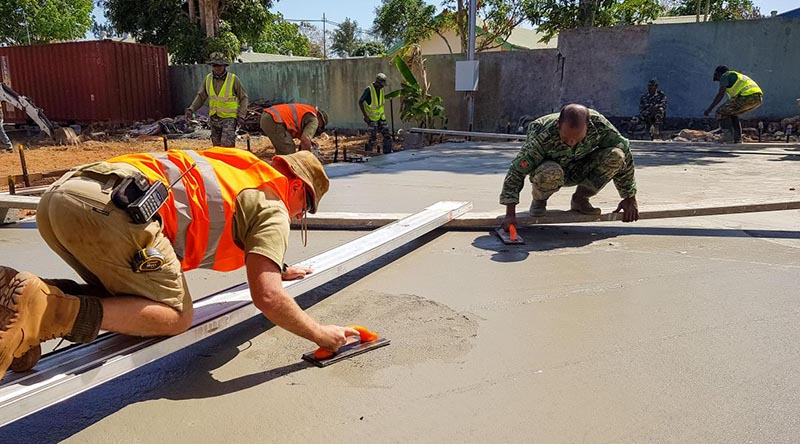 Corporal Gary Beattie, left, works alongside Timor-Leste Defence Force soldiers on a construction site during Exercise Hari'i Hamutuk 2020. Photo by Captain Caitlin McDermid.