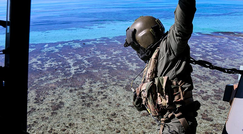 Petty Officer Rhys Withers in an MRH-90 helicopter looks over Elizabeth Reef during an unexploded ordnance clearance mission. Photo by Sergeant Jake Sims.