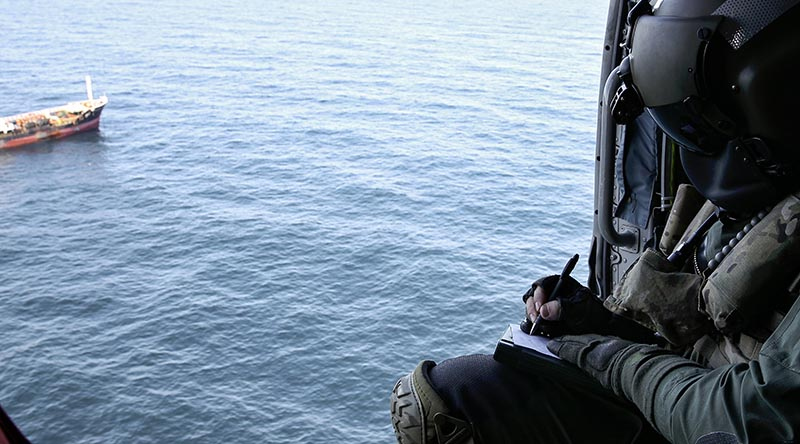 Leading Seaman Aircrewman Brad Firkin collects information on a vessel of interest from HMAS Arunta's MH-60R Seahawk helicopter during Operation Argos. Photo by Leading Seaman Jarrod Mulvihill.