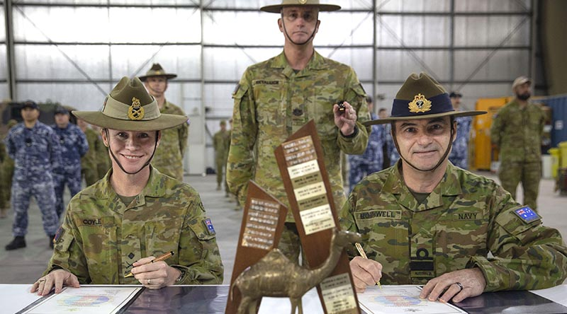 Outgoing Commander of Joint Task Force 633 Major General Susan Coyle and her replacement, Rear Admiral Michael Rothwell sign the papers to transfer command of Australian forces in the Middle East, watched by incoming Command Warrant Officer WO1 Mark Retallick. Photo by Sergeant Ben Dempster.