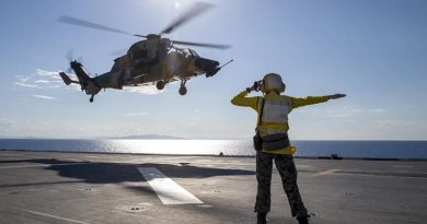 Able Seaman Lily Hardin waves off an Army ARH-Tiger as it takes off from the deck of HMAS Adelaide near Townsville during Exercise Sea Wader. Photo by Leading Seaman Nadav Harel.