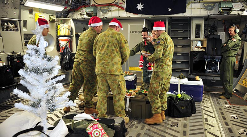 Aircrew from No. 36 Squadron, RAAF Base Amberley, enjoy a semi-traditional Christmas lunch onboard a C-17A Globemaster in transit to the Middle East. Photo by Sergeant W Guthrie.