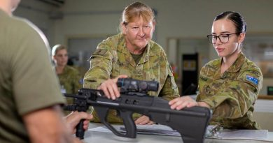 Warrant Officer Class 2 Cheryl Peebles, centre, with a soldier signing out a weapon from the armoury at Camp Baird in the Middle East region. Photo by Corporal Tristan Kennedy.
