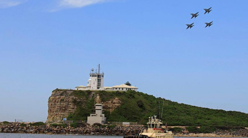 A formation of four F/A-18A/B Hornets over the lighthouse at Nobbys Beach in Newcastle. Photo by Corporal Brett Sherriff.