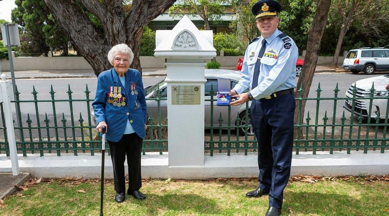 Senior Australian Defence Force Officer - Edinburgh Defence precinct Air Commodore Brendan Rogers presents a US Army Small Ships Section medallion to World War II veteran Thelma Zimmerman. Photo by Leading Aircraftwoman Jacqueline Forrester.