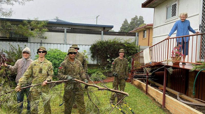 Connor Nish, left, and 41st Battalion, Royal New South Wales Regiment, soldiers Private Callum Nish, Private John Koronui, Corporal Paul Kohlhagen and Private Tom Mackney remove branches from Myrie McPherson's backyard.