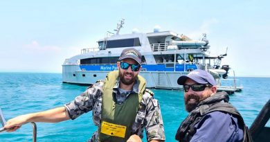 ADV Cape Inscription Navigation Officer Lieutenant Rhys Worboys and Great Barrier Reef Marine Park Authority officer Dwaine Butcher in front of Reef Ranger, a Queensland Parks and Wildlife Service vessel.