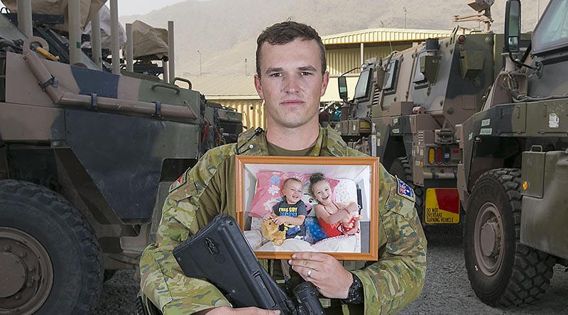Private Kieren Morrissey, from Dubbo, deployed with Force Protection Element 10 on Operation Highroad in Kabul, Afghanistan, holds a photo of his children Aria and Sloane, on Father's Day 2018. Photo by Petty Officer Andrew Daken.