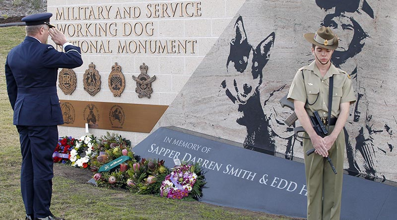 Commander Combat Support Group, Air Commodore Tim Innes, representing the Chief of Air Force, salutes the fallen after laying a wreath at the Military and Service Working Dog National Memorial. Photo by Corporal Peter Borys.
