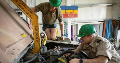 Lance Corporal Cameron Pennell, left, and Rear Admiral Michael Rothwell begin removing the engine from a protected mobility vehicle in the Middle East region. Photo by Sergeant Ben Dempster.