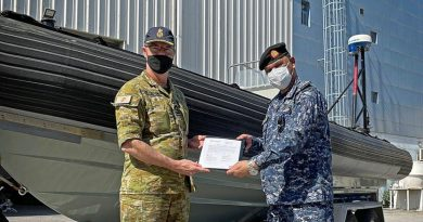 Commander of the Maritime Task Group – Middle East Region Captain Bruce Willington, left, presents the rigid hull inflatable boat to Bahrain Defence Force Captain Adel Salem Almeeri.