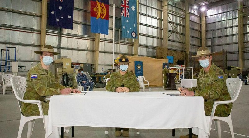 Major Justin Tomlinson, left, signs over authority to Major Simon Watch, right, with Commander JTF633 Rear Admiral Michael Rothwell. Photo by Sergeant Ben Dempster.