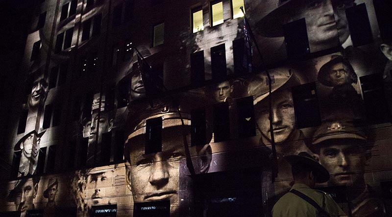Faces of Australian war veterans projected on a facade in Martin Place, Sydney, during an Anzac Day dawn service. Photo by Able Seaman Bonnie Gassner.