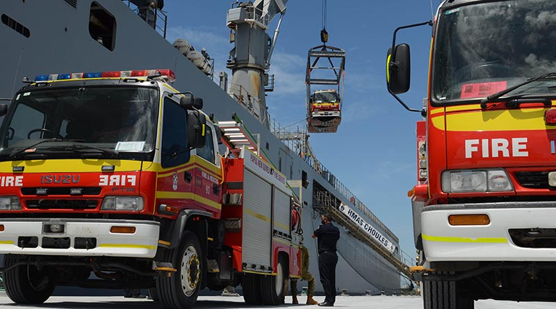 A Queensland Fire and Emergency Service fire truck is loaded onto HMAS Choules in Brisbane, while another two await loading, ahead of their transportation to Papua New Guinea. Photo by Major Anna-Lise Brink.