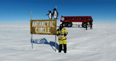 Sergeant Michelle Espley from No. 23 Squadron at the Antarctic Circle sign during Operation Southern Discovery.