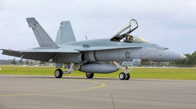 Caption: An Air Force F/A-18A Hornet aircraft from No. 77 Squadron taxis for the final time at RAAF Base Williamtown, New South Wales.