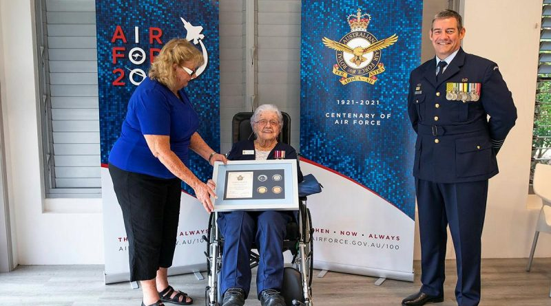 Wilma Ayles, centre, supported by her daughter Evelyn Schuetze, receives an Air Force 2021 memento from Senior ADF Officer Amberley Group Captain Iain Carty at Cooroy, Queensland. Photo by Leading Aircraftwoman Emma Schwenke.