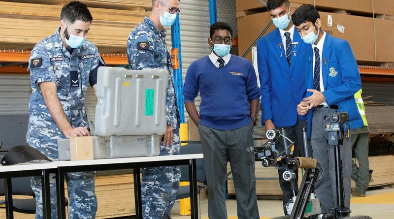 Leading Aircraftman Chris Carrigan, left, and Leading Aircraftman Jordan Hopkins demonstrate a vehicle used to detect Improvised Explosive Devices to Patrician Brothers students Amarjith Ajith, Agam Gujral and Damien Sinha, Photo by Corporal Kylie Gibson.