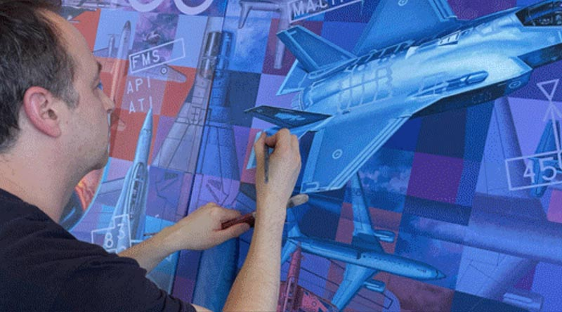 Australian aviation artist Drew Harrison puts finishing touches on the artwork he was commissioned to paint to mark the Centenary of the Royal Australian Air Force. Image supplied.
