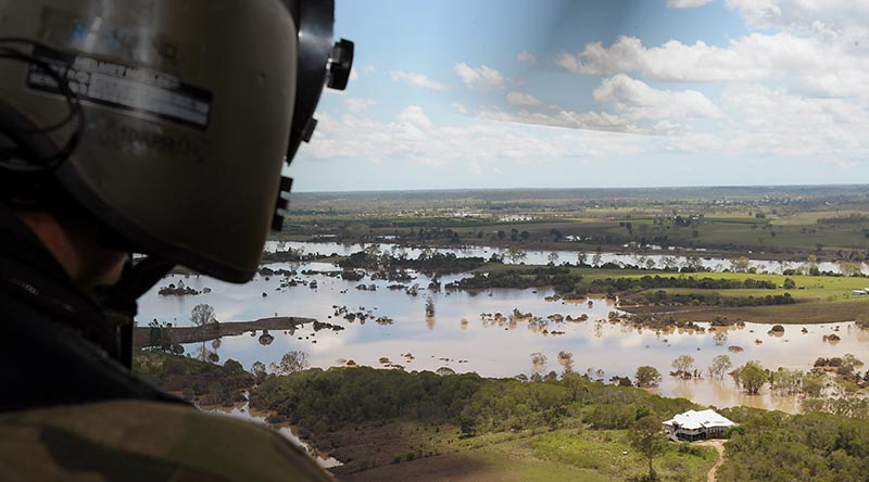 A helicopter loadmaster surveys floodwaters near Bundaberg, Queensland (2013). Photograph by Corporal Janine Fabre.