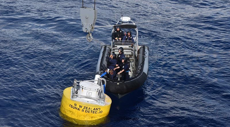 A RHIB crew from HMNZS Aotearoa secures the tsunami-detection buoy in preparation for the ship's crane to lift it aboard. NZDF photo.