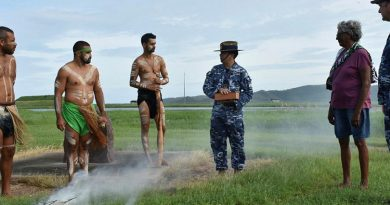 Les Tanna, left, Ashley Saltner, Glen Thomas, Flight Lieutenant David Williams holding soil from Wulgurukaba land, Virginia Wyles and Wing Commander Mathew Green at RAAF Base Townsville. Photo by Corporal Luke Garner.