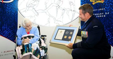 Senior Australian Defence Force Officer RAAF Base Amberley Group Captain Iain Carty presents Air Force veteran Mary Collins with an Air Force 2021 commemorative memento in celebration of her 100th birthday. Photo by Corporal Brett Sherriff.