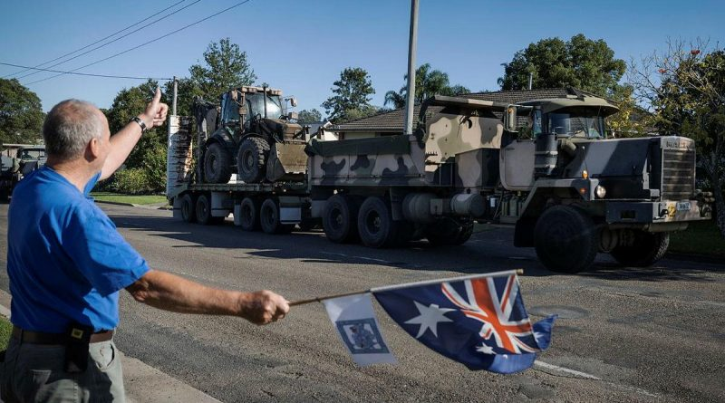 Darcy Elbourne waves the Australian flag in the driveway of his home as Army personnel head out to conduct relief and recovery tasks during Operation NSW Flood Assist in Taree. Photo by Corporal Sagi Biderman.